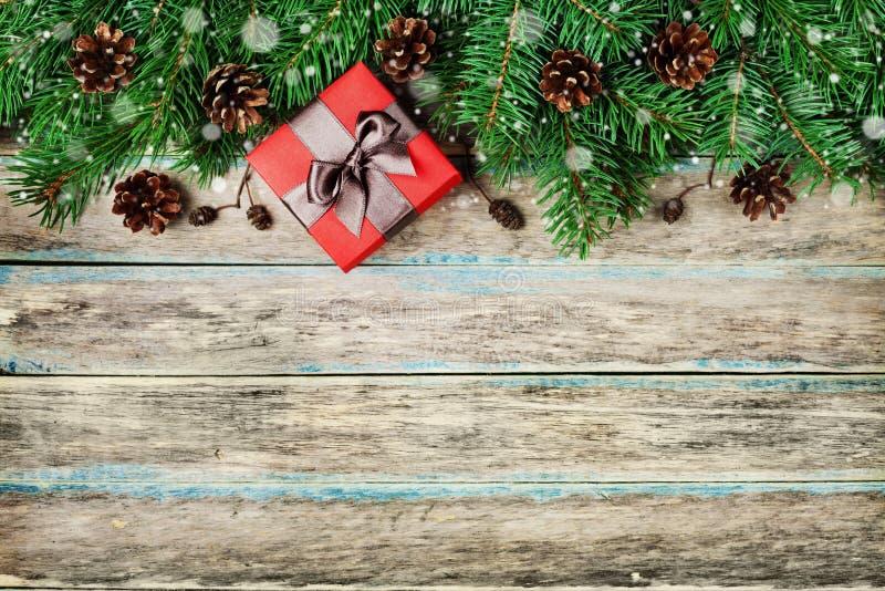 Bożenarodzeniowy tło z prezenta pudełkiem, jodły gałąź i conifer rożkiem na drewnianej wieśniak desce, świąteczny śnieżny skutek, obrazy royalty free