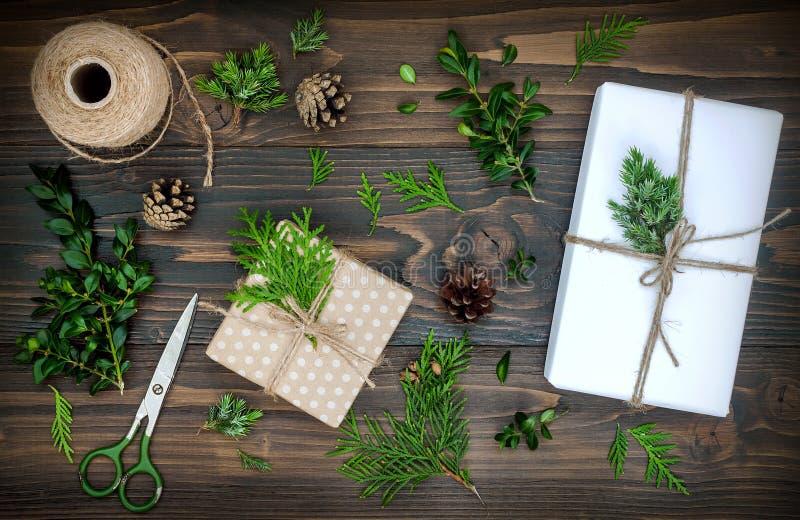 Bożenarodzeniowy tło z ręką wykonywał ręcznie prezenty, teraźniejszość na nieociosanym drewnianym stole Bożenarodzeniowy DIY koco zdjęcie royalty free