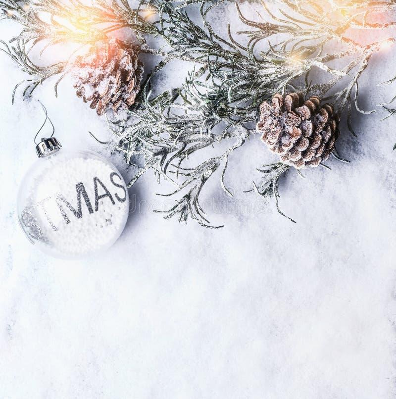 Bożenarodzeniowy tło z szklanym xmas bauble, marznąć gałąź i rożkami na śniegu z, opad śniegu i bokeh, zdjęcia stock