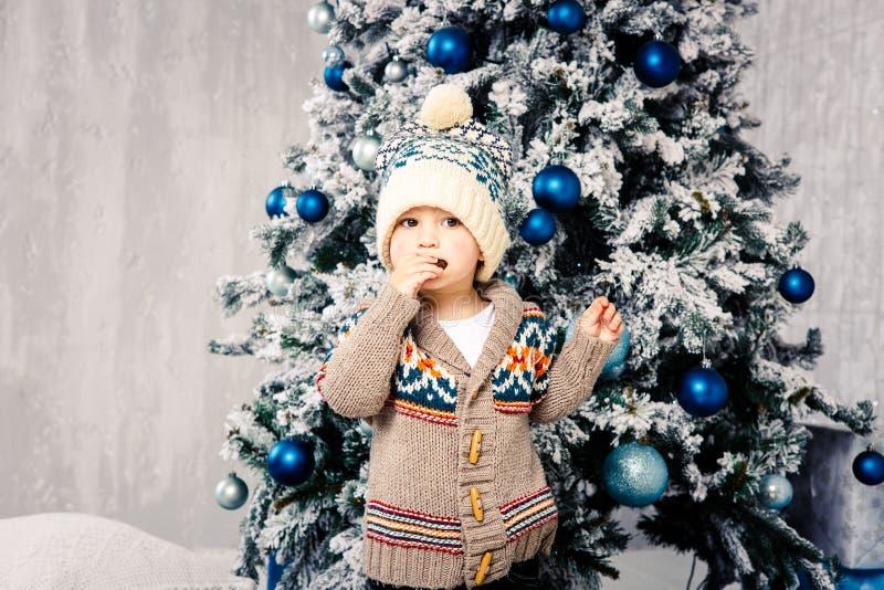 Bożenarodzeniowy temat i dzieci Mały Kaukaski chłopiec dziecko w ciepły kapeluszu i puloweru pozować, je słodkość, brudzi twarz B fotografia stock