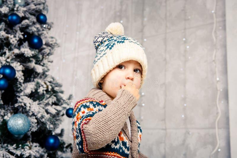 Bożenarodzeniowy temat i dzieci Mały Kaukaski chłopiec dziecko w ciepły kapeluszu i puloweru pozować, je słodkość, brudzi twarz B zdjęcia stock