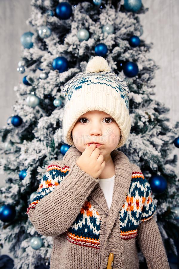 Bożenarodzeniowy temat i dzieci Mały Kaukaski chłopiec dziecko w ciepły kapeluszu i puloweru pozować, je słodkość, brudzi twarz B zdjęcia royalty free