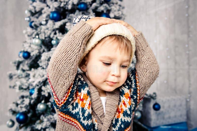 Bożenarodzeniowy temat i dzieci Mały Kaukaski chłopiec dziecko w ciepły kapeluszu i puloweru pozować, je słodkość, brudzi twarz B obrazy royalty free
