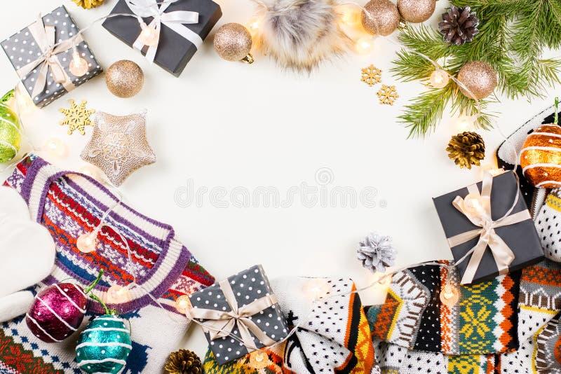 Bożenarodzeniowy trybowy skład z Bożenarodzeniowym pulowerem, kapelusz, przedstawia i zaświeca Zimy pojęcia mieszkanie nieatutowy obraz stock