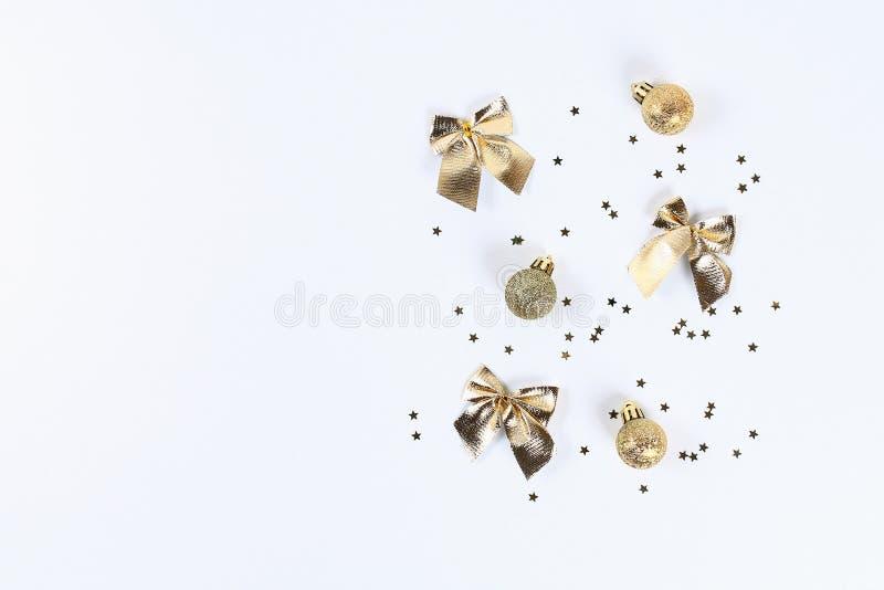 Bożenarodzeniowy układ Złoci confetti w postaci gwiazd, zabawkarskiej piłki i łęków na białym tle, Nowy Rok 2019, boże narodzenia obrazy royalty free