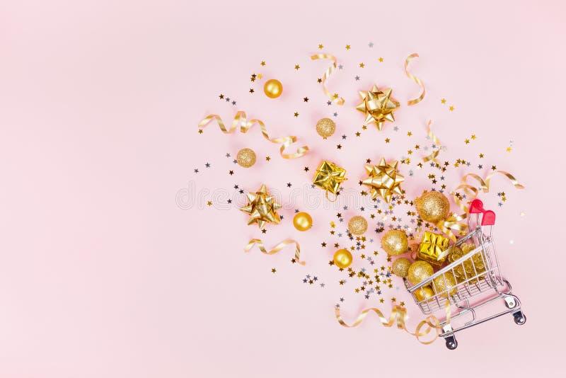 Bożenarodzeniowy wózek na zakupy z prezentem, wakacyjnymi dekoracjami i złotymi confetti na różowego pastelowego tła odgórnym wid fotografia stock