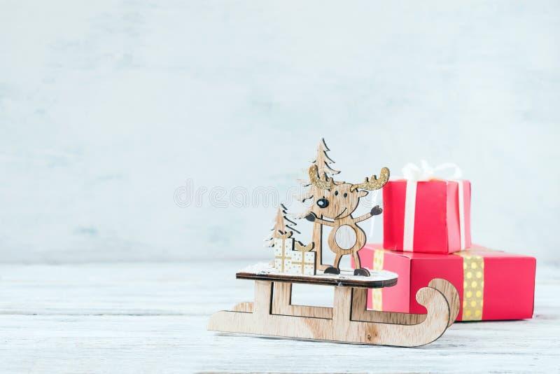 Bożenarodzeniowy wakacyjny świąteczny temat z drewnianym ślicznym reniferem na saniu, czerwoni prezentów pudełka na białym nieoci fotografia royalty free