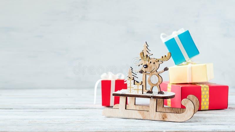 Bożenarodzeniowy wakacyjny świąteczny temat z drewnianym ślicznym reniferem na saniu, czerwoni prezentów pudełka na białym nieoci fotografia stock