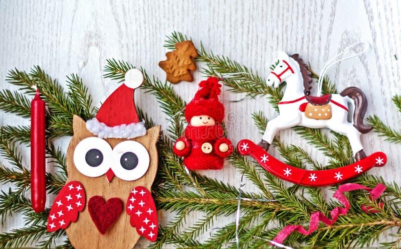 Bożenarodzeniowy wakacyjny tło z Bożenarodzeniowymi dekoracjami, sowa w Santa kapeluszu, zabawkarski koń na lekkim drewnianym sto zdjęcia stock