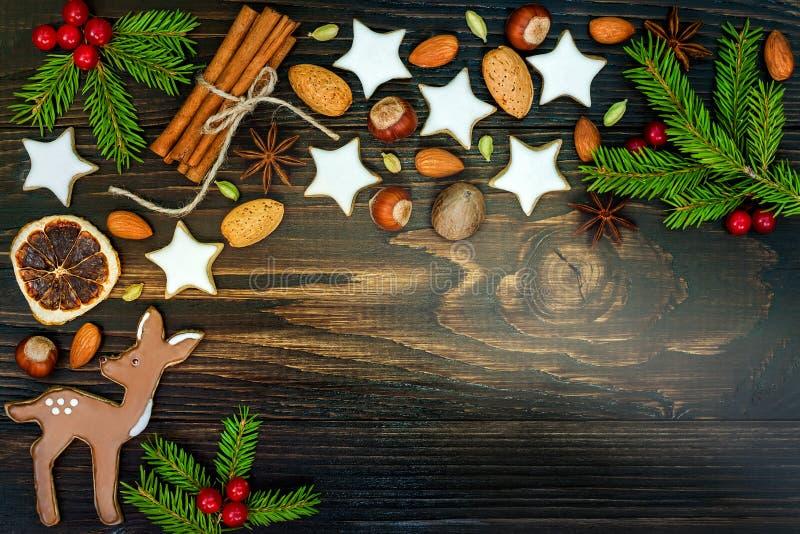 Bożenarodzeniowy wakacyjny tło z piernikowymi ciastkami i jodłą rozgałęzia się na starej drewnianej desce kosmos kopii fotografia royalty free