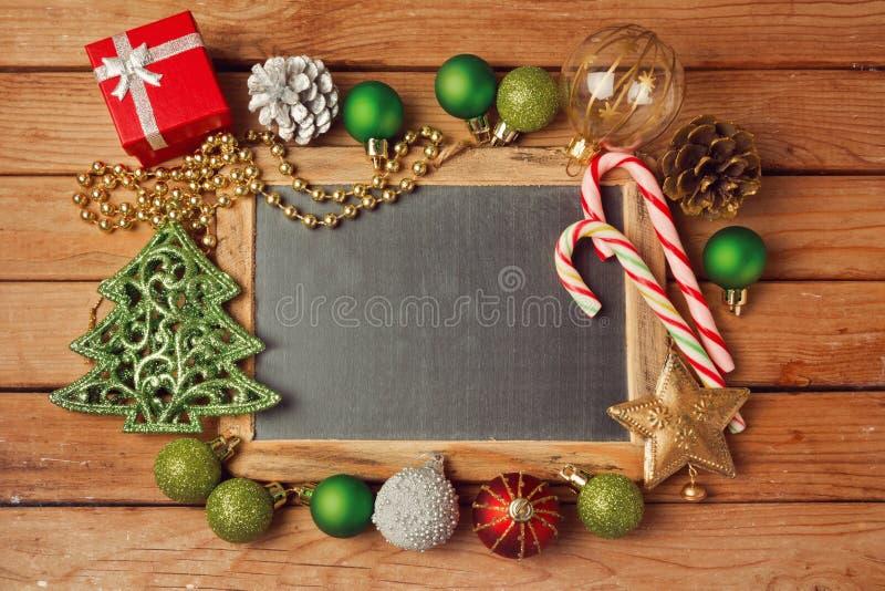Bożenarodzeniowy wakacyjny tło z pustym chalkboard na drewnianych stołowych i Bożenarodzeniowych dekoracjach zdjęcia royalty free