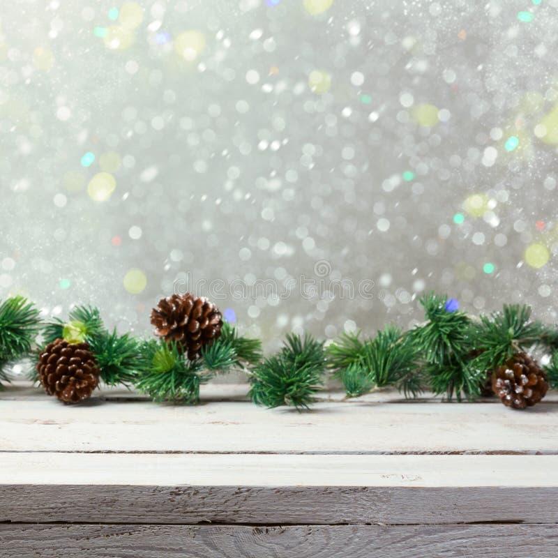 Bożenarodzeniowy wakacyjny tło z pustym drewnianym bielu stołem, bożonarodzeniowe światła i obraz stock