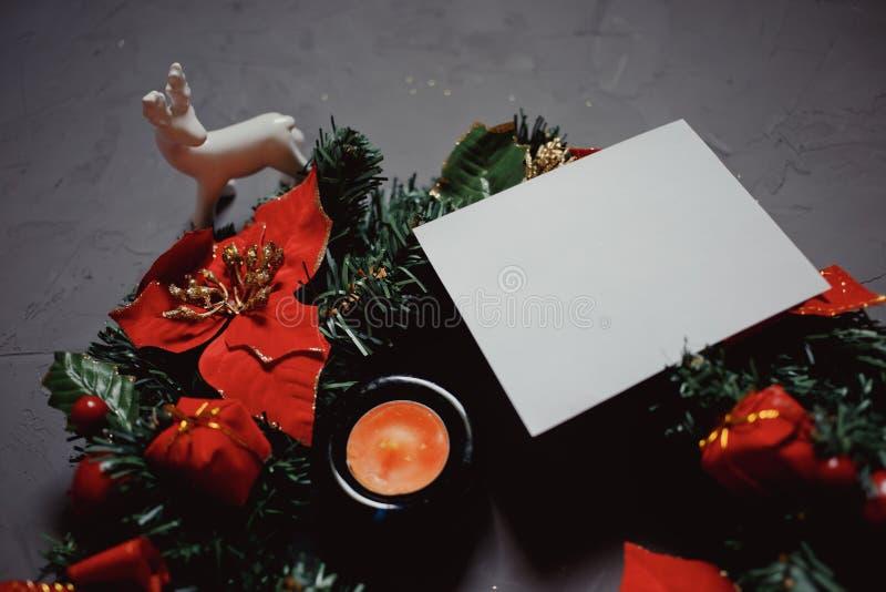 Bożenarodzeniowy wianek, biali porcelana rogacze, świeczka i kartka z pozdrowieniami na ciemnym textured tle, zdjęcie stock