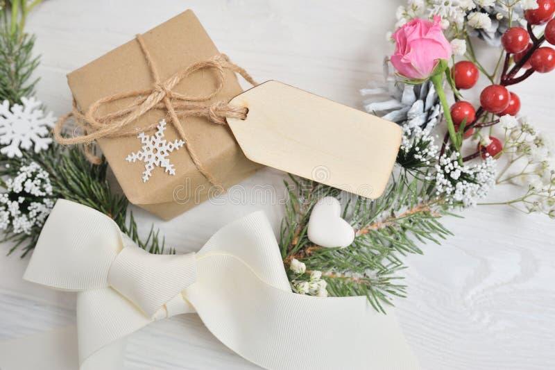 Bożenarodzeniowy wianku tło z pustą drewnianą etykietką dla twój teksta Ono kłania się, boże narodzenia prezenty, menchii róża i  fotografia royalty free