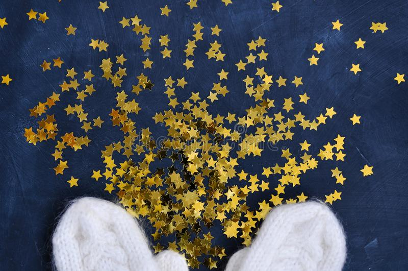 Bożenarodzeniowy Wygodny magiczny tło z białymi trykotowymi mitynkami i błyszczący złoto gramy główna rolę confetti na ciemnym tl zdjęcia royalty free