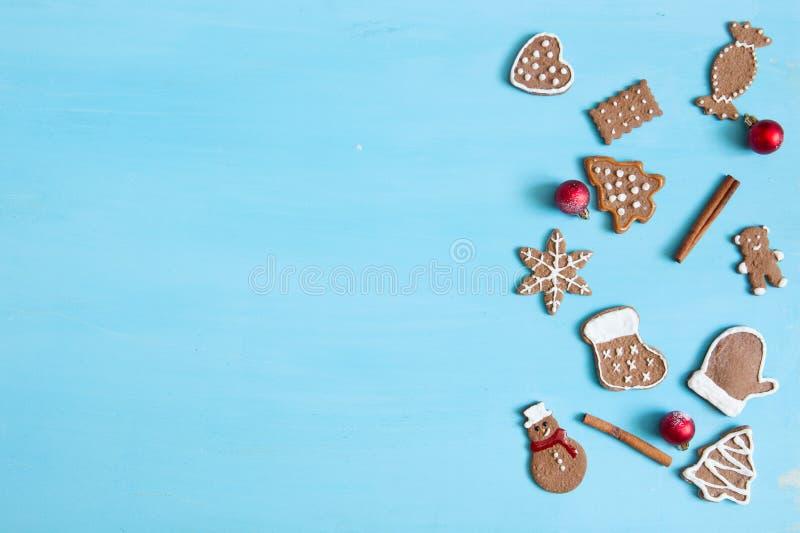 Bożenarodzeniowy wypiekowy tło Bożenarodzeniowi piernikowi ciastka i pikantność na błękita stole Odgórny widok obraz royalty free
