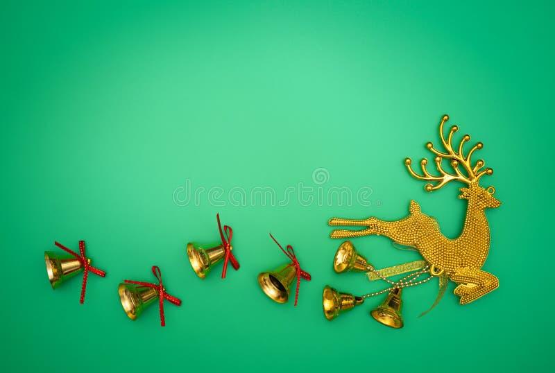 Bożenarodzeniowy złocisty reniferowy skład Bożenarodzeniowy prezent, złocisty renifer i dzwon na zielonym tle, Mieszkanie nieatut zdjęcie royalty free