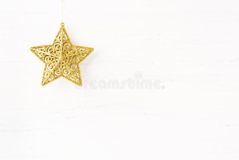 Bożenarodzeniowy złoty gwiazdowy ornament na białym drewnianym tle obraz royalty free