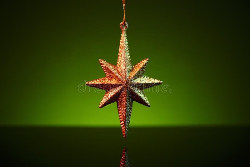 Bożenarodzeniowy złoty gwiazdowy ornament nad zielonym tłem zdjęcia royalty free