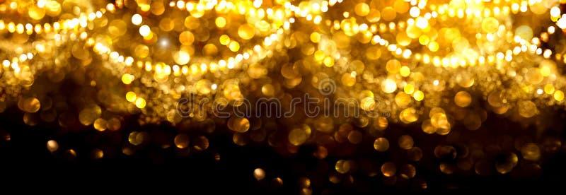 Bożenarodzeniowy złoty rozjarzony tło Złocistej wakacyjnej abstrakcjonistycznej błyskotliwości defocused tło z mruganie girlandam zdjęcia stock