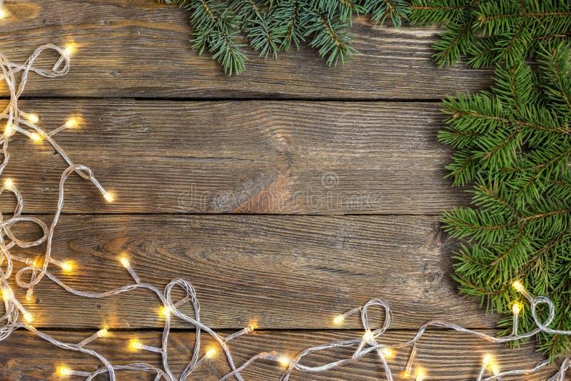 Bożenarodzeniowy zakończenie choinki Chistmas i gałąź zaświeca na rocznika drewnianym tle obrazy stock