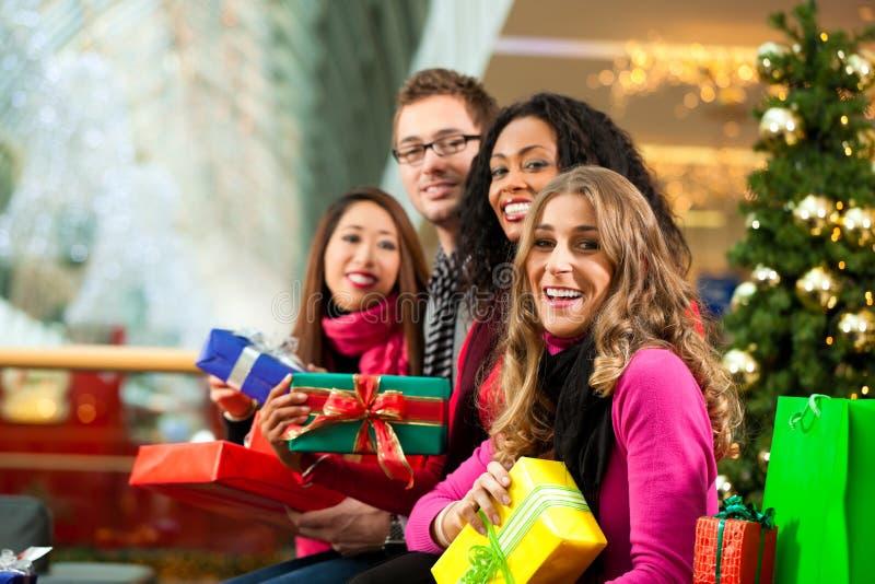 Bożenarodzeniowy zakupy - przyjaciele w centrum handlowym zdjęcie royalty free