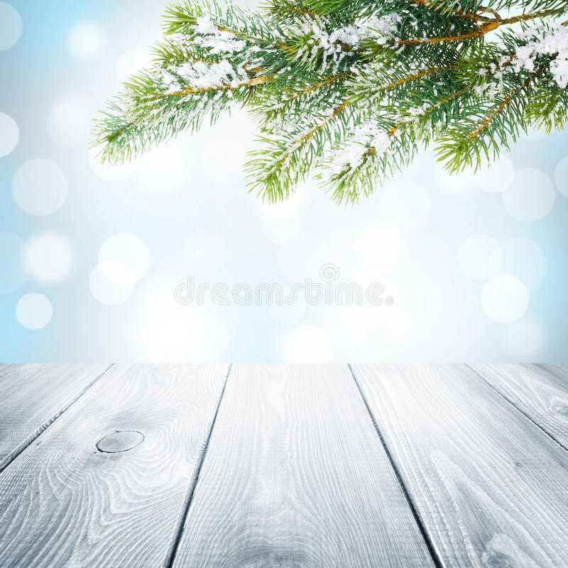 Bożenarodzeniowy zimy tło z śnieżnym jedlinowym drzewem i drewnianym stołem