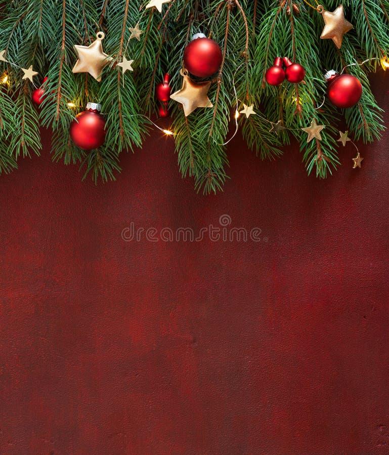 Bożonarodzeniowa granica z gałęziami jodłowymi, czerwonymi bąbelkami i złotymi gwiazdami na drewnianej tablicy pomalowana w ciemn zdjęcie royalty free