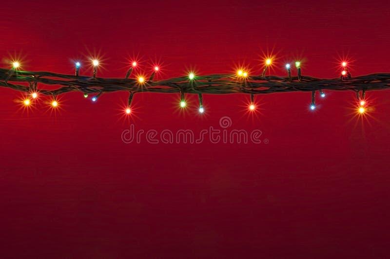 Bożonarodzeniowe światła na czerwonym tle Stubarwny lighton czerwieni tło zdjęcie stock
