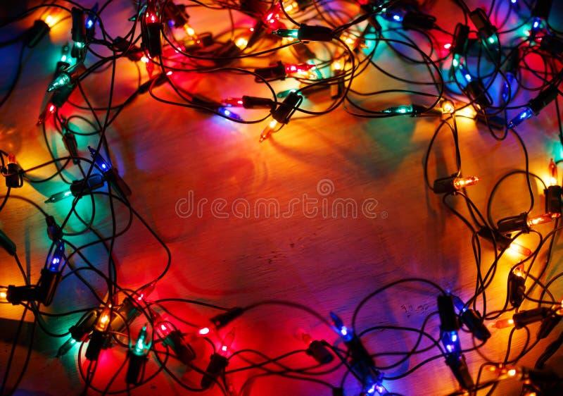 Bożonarodzeniowe światła obramiają na drewnianym tle fotografia stock