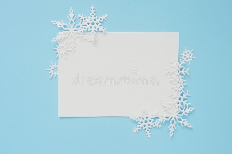 Bo?e Narodzenia lub zima sk?ad Rama biali płatek śniegu i biali cakle papier na pastelowym błękitnym tle Bo?e Narodzenia obraz royalty free