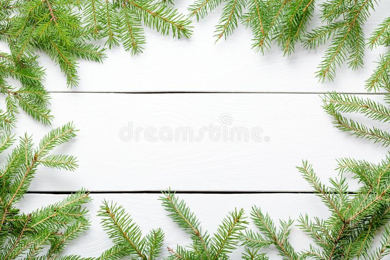 Bo?e Narodzenia obramiaj? t?o Bożenarodzeniowe jedlinowe gałąź na białej nieociosanej drewnianej desce z kopii przestrzenią zdjęcia royalty free