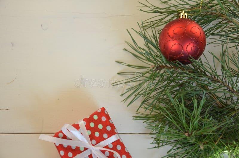 Bo?enarodzeniowy t?o z dekoracjami i prezent?w pude?kami na bia?ej drewnianej desce czerwona piłka, prezent wiązał z białym fabor obrazy stock