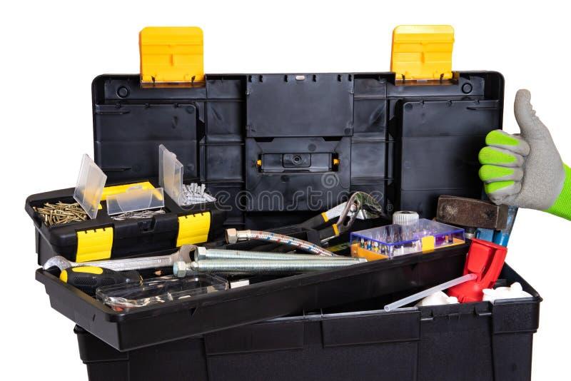 Bo?te ? outils d'isolement Boîte en plastique noire de trousse à outils avec les outils assortis et un gant montrant le pouce ver photographie stock libre de droits