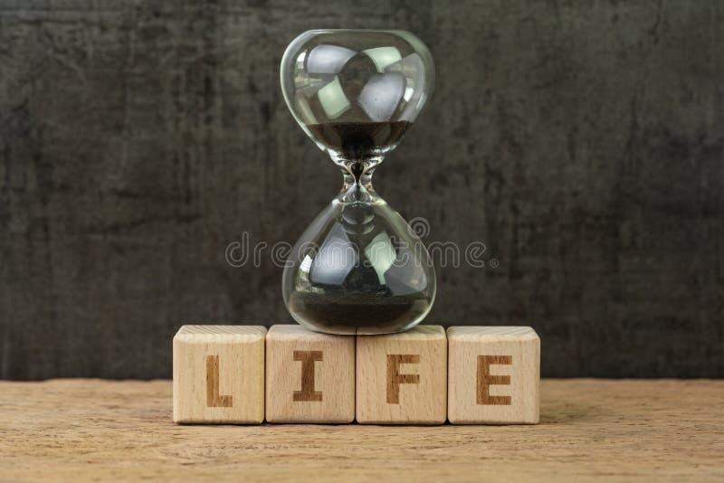 Bo tid för människolivnedräkning, livstid eller avgångbegrepp, sandglass eller timglas på träkubkvarteret med alfabet fotografering för bildbyråer