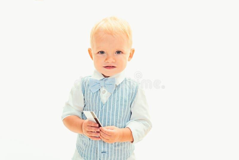 Boa compra Criança do menino com cartão de crédito Pouco possuidor de cartão O rapaz pequeno mantém o cartão A criança pequena fa foto de stock