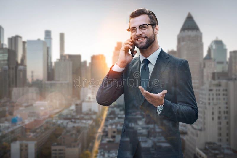 Boa conversa do negócio Homem de negócios alegre e à moda que fala com o cliente pelo telefone ao estar fora com arquitetura da c fotografia de stock royalty free