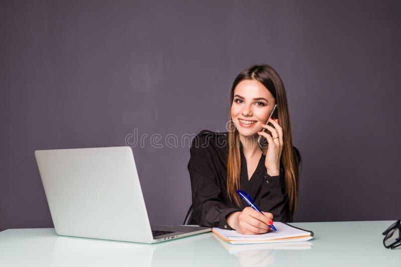 Boa conversa do negócio Mulher bonita nova alegre nos vidros que fala no telefone celular e que usa o portátil com sorriso ao sen fotografia de stock royalty free