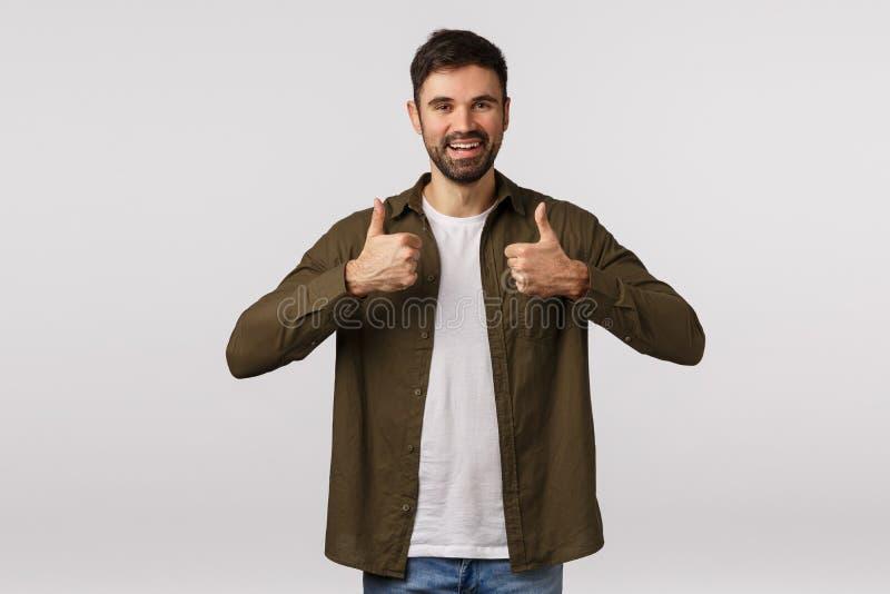 Boa ideia, amigo de apoio encoraje a agir, como ideia Homem barbudo atrativo no casaco, mostre os polegares e foto de stock royalty free