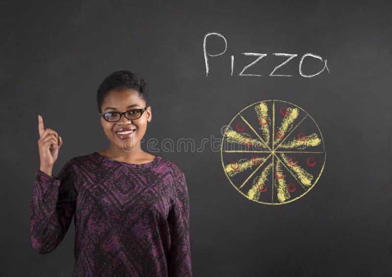 Boa ideia da mulher africana para a pizza no fundo do quadro-negro imagem de stock