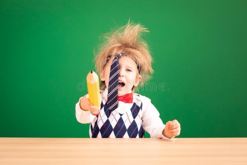 Boa ideia! Feliz estudante infantil contra o quadro verde imagens de stock