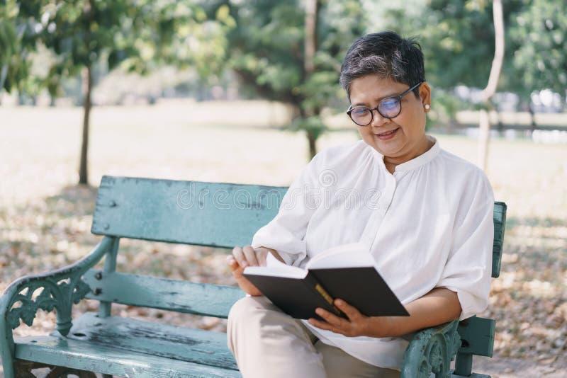 Boa idosa asiática sentada no banco no parque Conceito de vida feliz na aposentadoria fotografia de stock royalty free