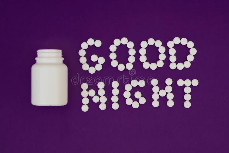 Boa noite da inscri??o feita dos comprimidos brancos Garrafa de comprimido no fundo violeta Conceito da ins?nia imagens de stock