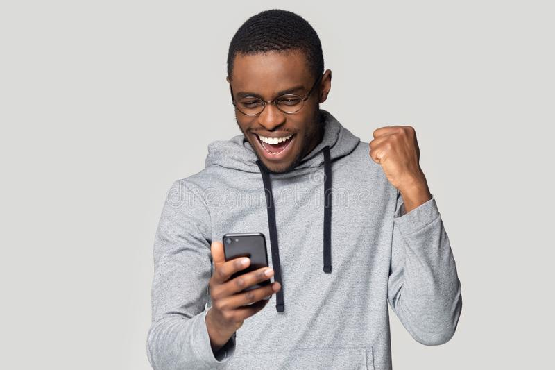 Boa notícia da leitura extático entusiasmado da sensação do homem negro no telefone celular imagens de stock