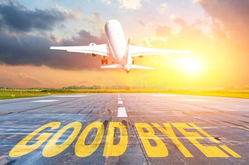 Boa sorte escrita no aeroporto da pista de decolagem, e o avião para decolar no por do sol Conceito da casa do retorno da partida fotos de stock royalty free