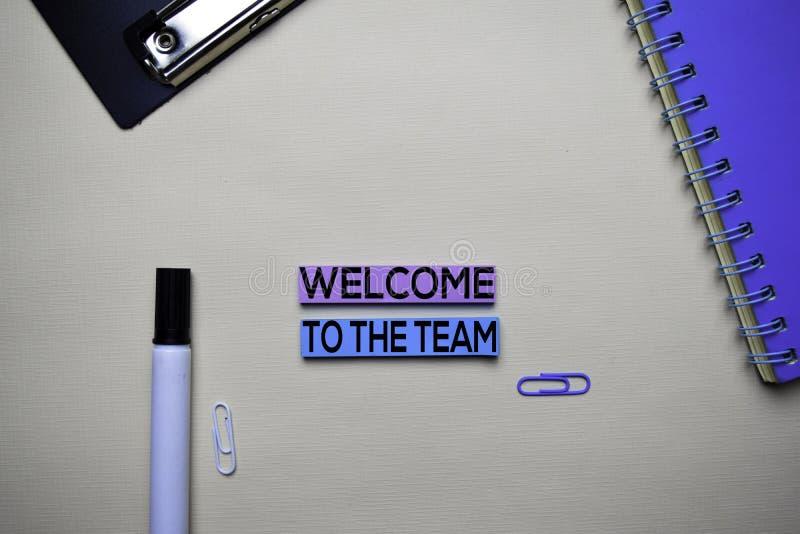Boa vinda ao texto da equipe em notas pegajosas com conceito da mesa de escritório imagem de stock