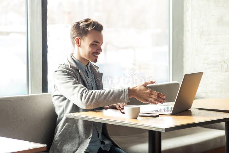 Boa vinda! O retrato do homem novo feliz satisfeito no blazer cinzento está sentando-se no café e está cumprimentando-se um traba imagens de stock