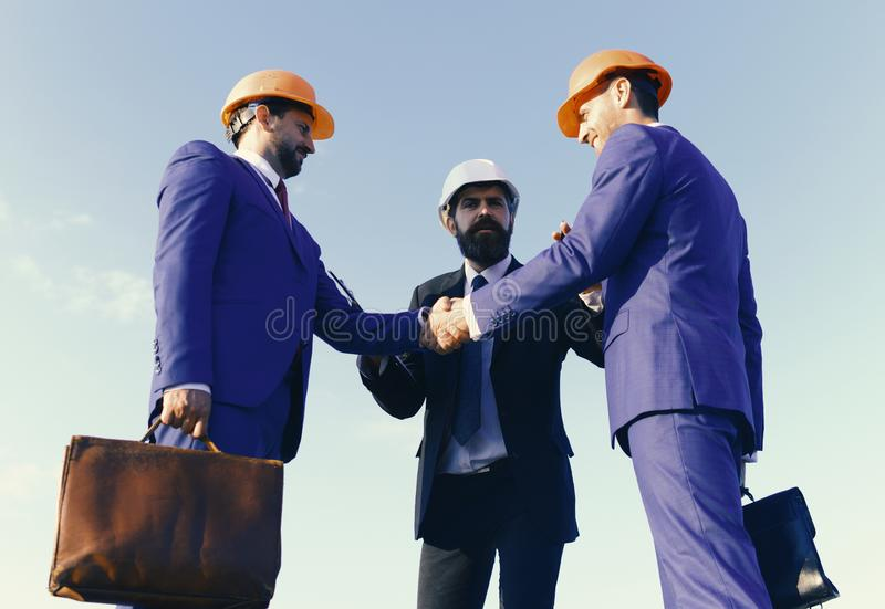Board of architects with serious faces in suits made deal stock photos