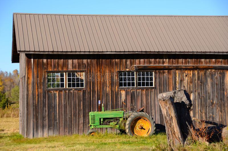 Board and batten vintage barn with tractor. To preserve barns and buildings in the olden days they were constructed with vertical boards to let rain run off flow royalty free stock photo