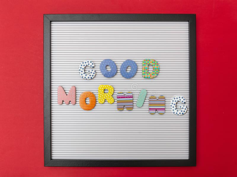 Board with black frame, text Good morning in colorful letters, red wall background stock photo